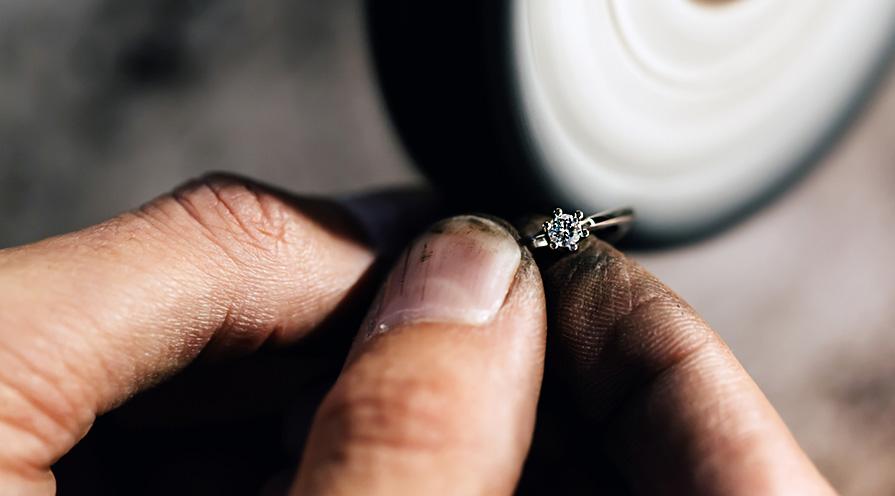 guldsmed som jobbar med slipning av ring i platina