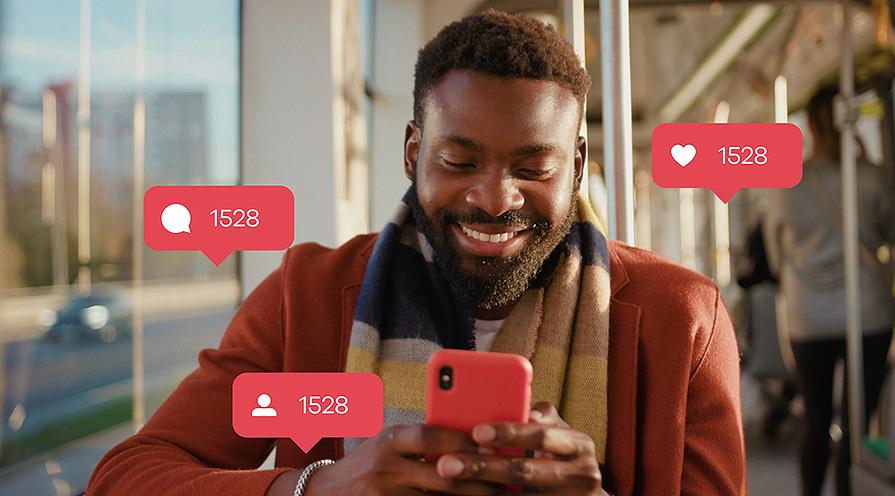 Man som ser likes i sin mobil