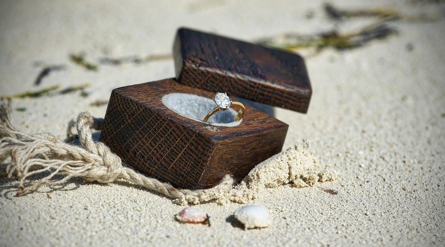 ask på strand med en diamantring
