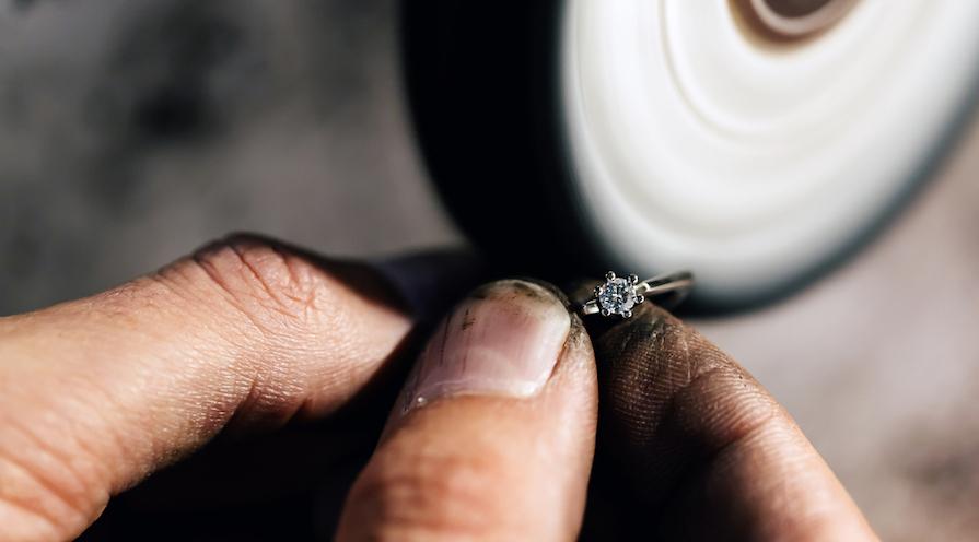 Guldsmed som arbetar med en ring
