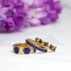 Tre guldringar med blå stenar, blommor