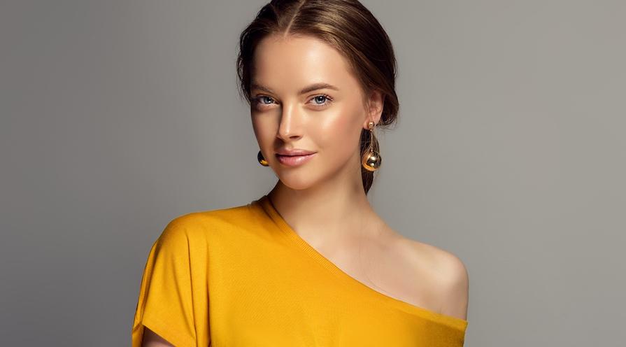 Tjej med guldsmycken och gul topp perfekt i påsk