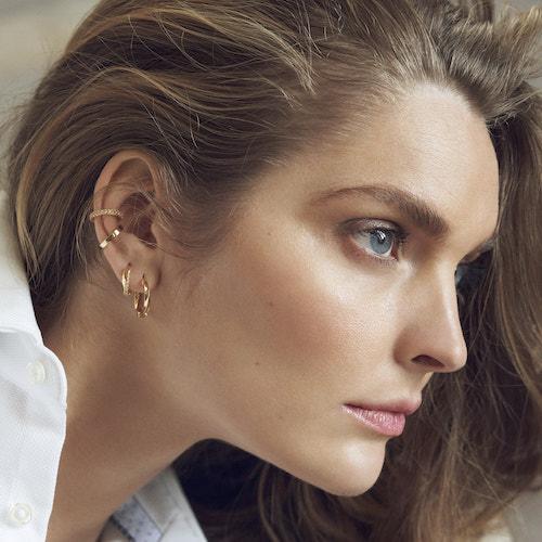 Kvinna med många örhängen i ett öra