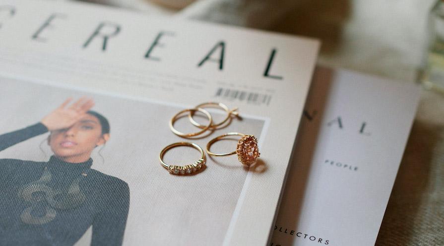 Guldringar liggandes på ett magasin - köpa smycken till sig själv