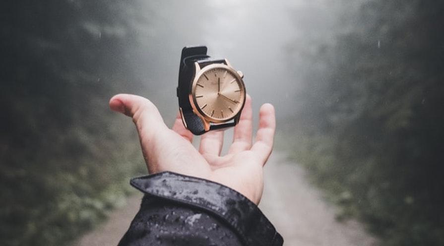 hand som håller i en klocka